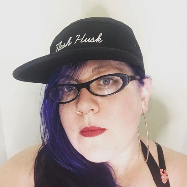Photo of Jess with black hat reading 'Flesh Husk' in cursive script